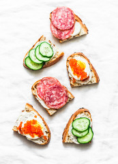 Appetizer sandwiches with red caviar, egg, sausage, cucumber and cream cheese on white background, top view