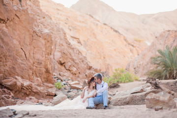 Beautiful wedding couple in the canyon kisses against the backdrop of palm trees