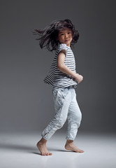 Happy Asian little girl playing in the studio