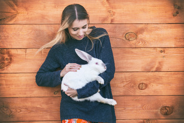 Young beautiful woman with a white rabbit in her arms next to a wooden house in the countryside