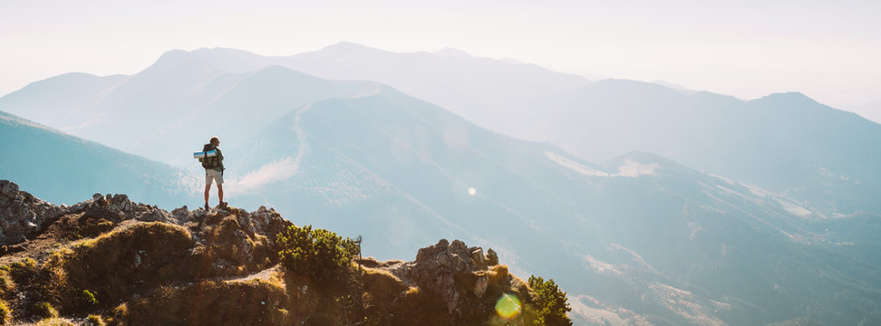 Mountain hiker with backpack tiny figurine stay on mountain peak with beautiful panorama