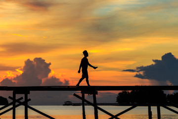 silhouette kids walk on the wooden jetty during sunset at Mantanani Island, Kota Belud, Sabah, Malaysia