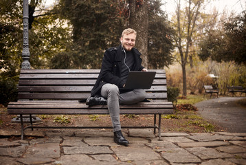 one young smiling and happy man, sitting on bench in public park,  using laptop, looking to camera. Formal wear or smart casual. Full length shot.
