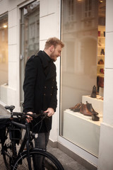 one young man, 20-29 years old, shopping for fancy shoes. standing in front of a store with his bicycle, looking to a window shop.