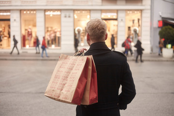 one young mans back, rear view, 20-29 years old, standing on a pedestrian street in city, looking, while holding two shopping bags on his back. Store front windows in distance.