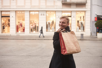 one young smiling man, rear view, 20-29 years old, standing on a pedestrian street in city, looking, while holding two shopping bags on his back. Store front windows in distance.