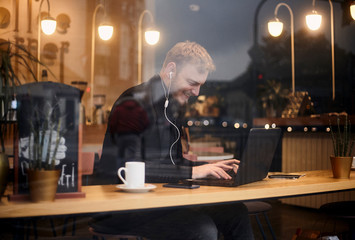 one young smiling man, 20-29 years, sitting in coffee shop and using, typing on keyboard of his laptop. Shoot thought window outside (with reflections from outside).
