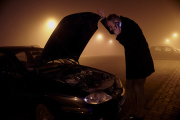 one young man, at dark night, looking at car engine, with car hood open. rural area.