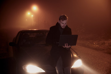 one young man using his laptop computer, on a car hood. It's dark and night time, in rural area.