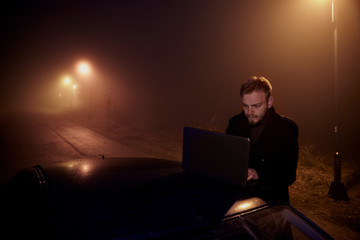 one young man, working (using) his laptop computer on a car roof, in dark night, rural area.