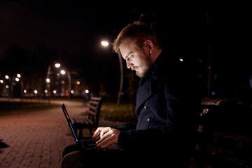 dark night, one young man, 20-29 years, sitting on bench alone, using his laptop typing on keyboard, in public park in Autumn.