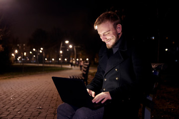 dark night, one smiling young man, 20-29 years, sitting on bench alone, using his laptop in public park in Autumn.