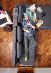 one young hipster man, laying in bed sleeping. whole sofa and bed visible, view from above.
