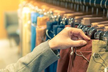 Hand of woman choosing pants more color hang on rack in department store.