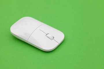White wireless optical mouse with a wheel on a green background. Modern concept for the Internet web site. Free space for input text, image, and logo. Mockup