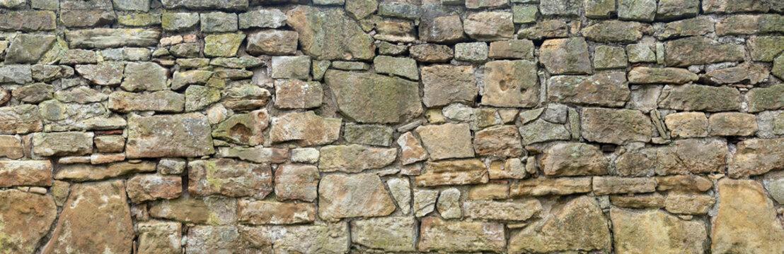 Panorama einer groben, sehr alten Natursteinmauer aus unterschiedlich großen Steinen