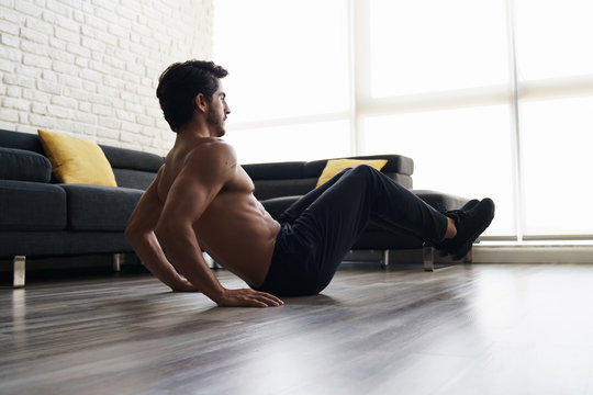 Muscular Attractive Young Man Doing Workout Abs Routine At Home