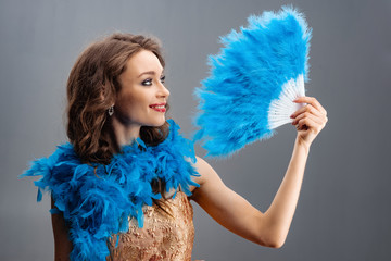 Beautiful young girl in a blue boa holding a fan of feathers in his hand