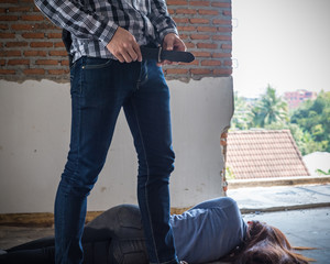 Sexual abuse with a terrorist attacking a scared female in abandon building. Rape and Sexual abuse concept.dark tone