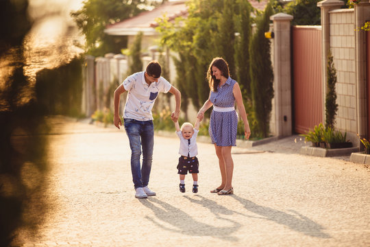 Mom, Dad and son. The family strolls through the streets of the city near houses