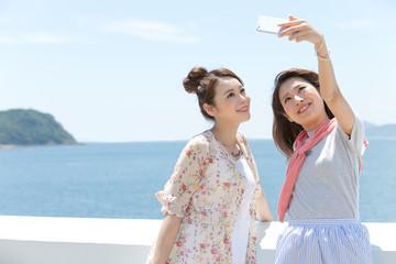 スマートフォンで写真を撮る女性2人
