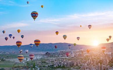 Poster Ballon Colorful hot air balloons flying over rock landscape at Cappadocia Turkey