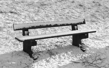 black and white photo of a bench in the park covered with snow in winter