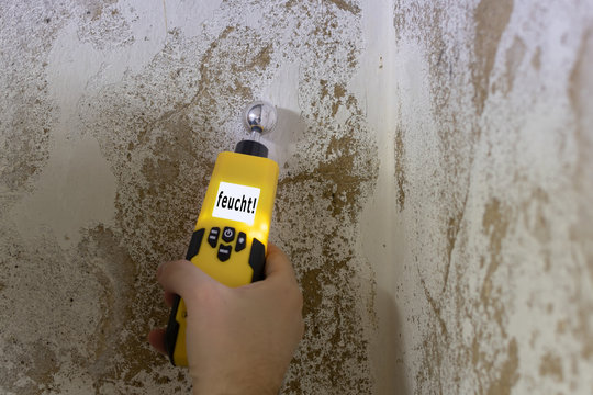 Mit einem Feuchtigkeitsmessgerät wird eine Kellerwand gemessen. Das Messgerät zeigt an, dass die Wand feucht ist.