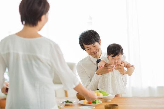 赤ちゃんの子守りをする父親と朝食の準備をする母親