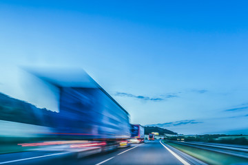 Background photograph of a highway. Truck on a motorway, motion blur, light trails. Evening or night shot of trucks doing logistics and transportation on a highway.
