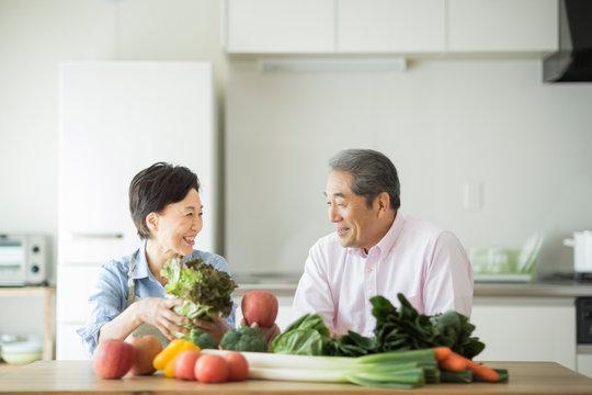 テーブルに置かれた野菜と笑顔のシニア夫婦