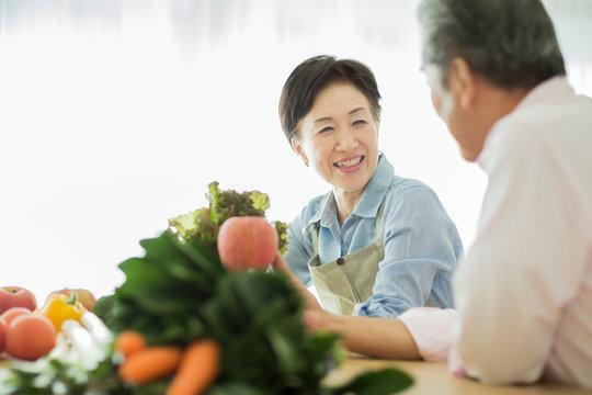 野菜を持って笑顔のシニア夫婦