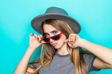 Fashion pretty woman wearing gray hat and sunglasses over colorful blue background