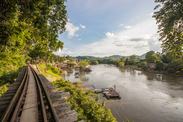 Railway between rocky cliff and river in Kanchanaburi, Thailand