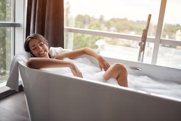 Relaxed woman lying in bathtub.