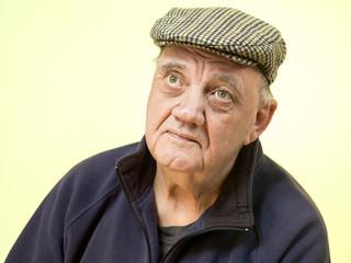 portrait homme âgé inquiet sur fond jaunâtre