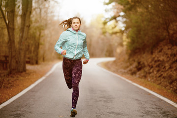 girl running on a road in the forest