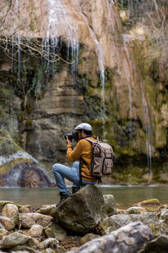 Side view of man taking picture with camera in forest
