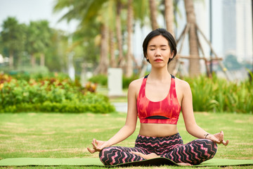Young Asian woman in sportswear sitting on mat in green summer park and meditating in peace