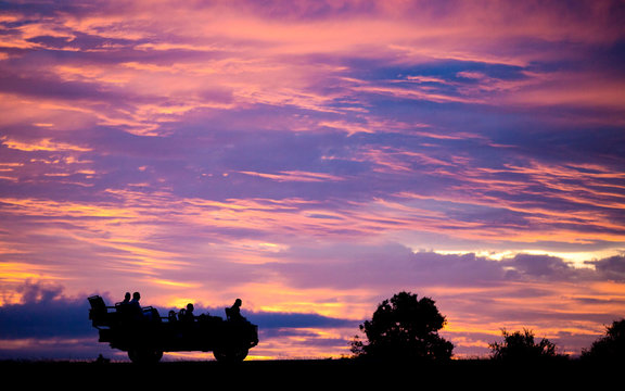 A silhouette of the side profile of people sitting in a Land Rover against pink, purple and yellow sunset sky.