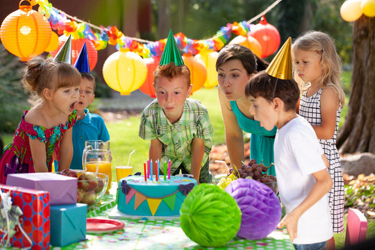 Redhead boy, his mother and friends blowing candles on birthday cake during garden party for children