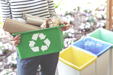Woman holding a green recycling basket filled with paper