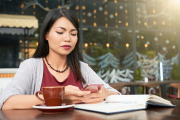Young attractive woman sitting at the table with notepad and cup of coffee and using her smartphone at outdoor cafe