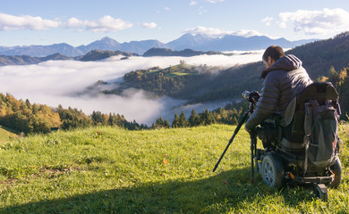 man on wheelchair taking photos of beautiful landscape in a foggy morning, St. Thomas Slovenia