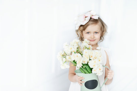 girl holding narcissus in hands. Adorable smiling little girl holding flowers for her mom on mother's day.