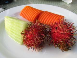 Exotic fruit on a plate. Rambutan, papaya