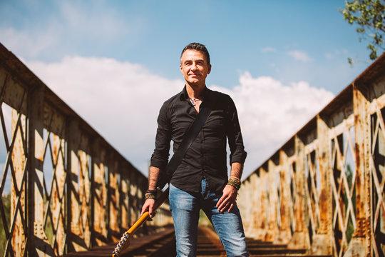 Man with guitar standing on bridge