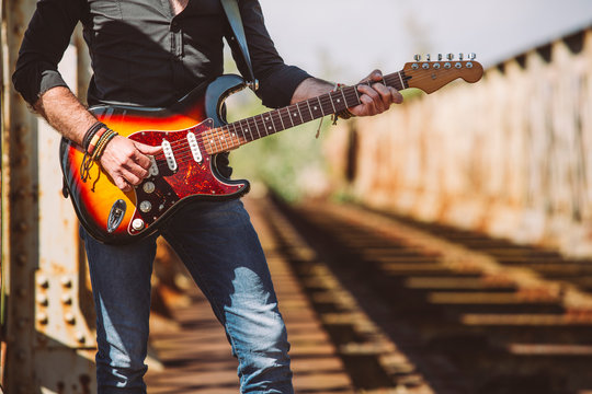 Midsection of man playing guitar on bridge