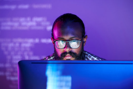 Young serious programmer in eyeglasses concentrating on working with coded data on computer screen
