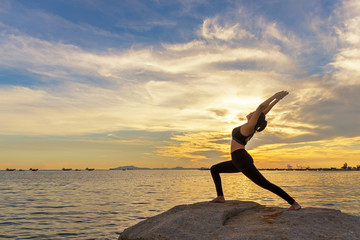 Fotobehang School de yoga Silhouette healthy woman lifestyle exercising vital meditate and practicing yoga outdoors on the rock at beach sunset and twilight time, city night background. Healthy Concept.